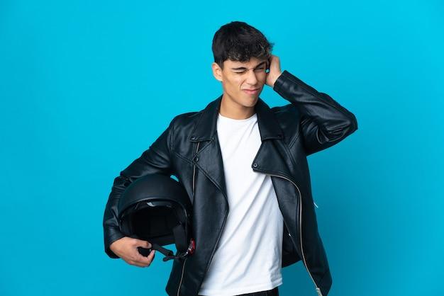 Jovem com um capacete de motociclista sobre uma parede azul isolada frustrado e cobrindo as orelhas