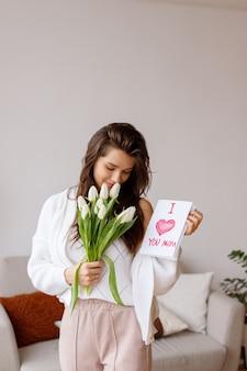 Jovem com um cartão postal e tulipas no dia internacional da mulher