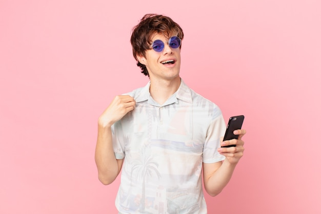 Jovem com um celular parecendo arrogante, bem-sucedido, positivo e orgulhoso