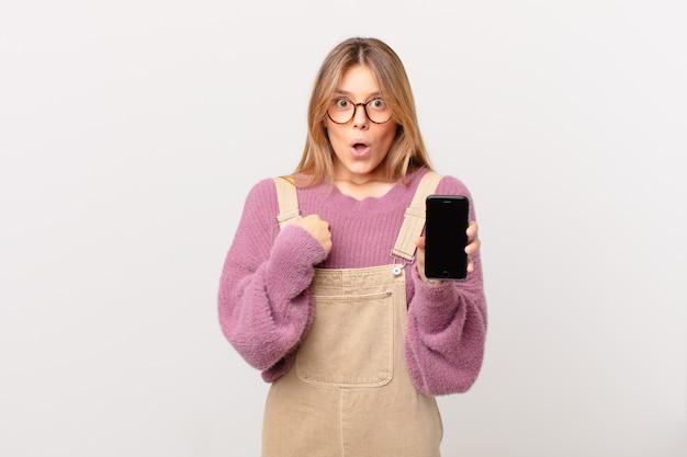 Jovem com um celular parecendo chocada e surpresa com a boca bem aberta, apontando para si mesma Foto Premium