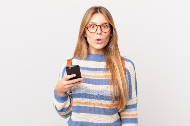 Jovem com um celular parecendo muito chocada ou surpresa