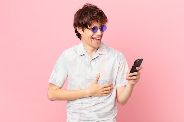 Jovem com um celular rindo alto de uma piada hilária