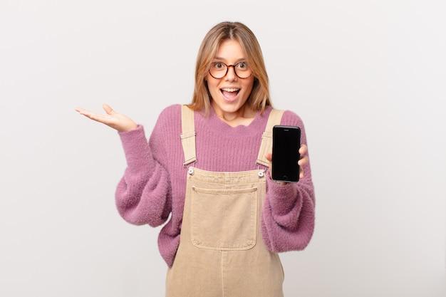 Jovem com um celular se sentindo feliz e surpresa com algo inacreditável