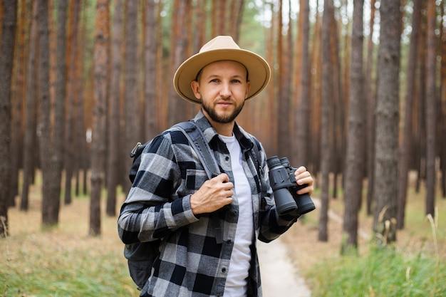 Jovem com um chapéu com uma mochila e binóculos em uma floresta de pinheiros. faça caminhadas nas montanhas ou na floresta.