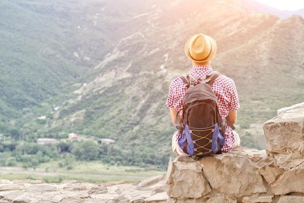 Jovem com um chapéu com uma mochila se senta em uma parede de pedra contra um fundo de montanhas verdes.