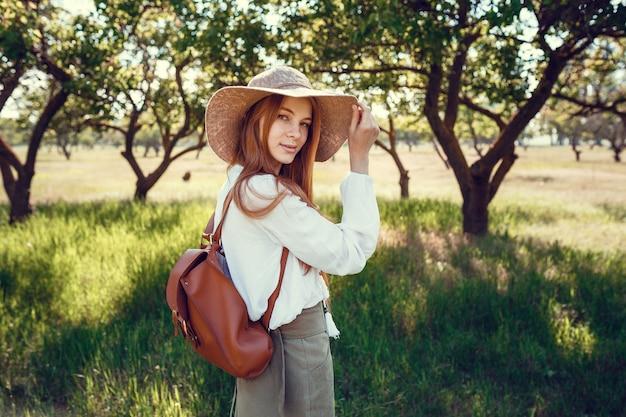 Jovem com um chapéu de palha viaja prados verdes. mulher linda ruiva hippie em um jardim verde