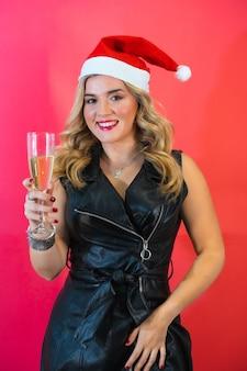 Jovem com um chapéu de papai noel e um elegante vestido preto posando com uma taça de champanhe