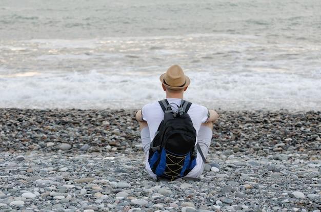 Jovem com um chapéu e uma mochila está sentado na praia ao fundo