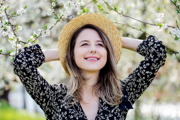 Jovem com um chapéu fica perto de uma árvore florida no parque. temporada de primavera
