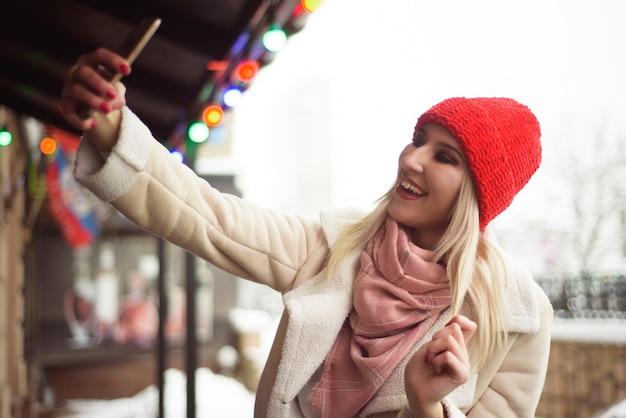 Jovem com um chapéu vermelho e luvas ao ar livre no inverno.