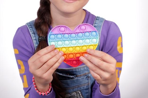 Jovem com um coração multicolorido de silicone nas mãos.