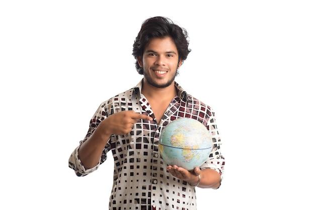 Jovem com um globo do mundo em um branco.