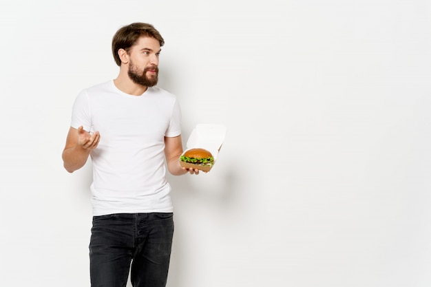 Jovem com um hambúrguer suculento nas mãos, um homem comendo um hambúrguer