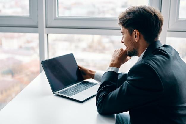 Jovem com um laptop em um terno de negócio trabalhando no escritório e em casa