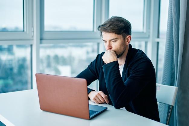 Jovem com um laptop funciona e tem um descanso