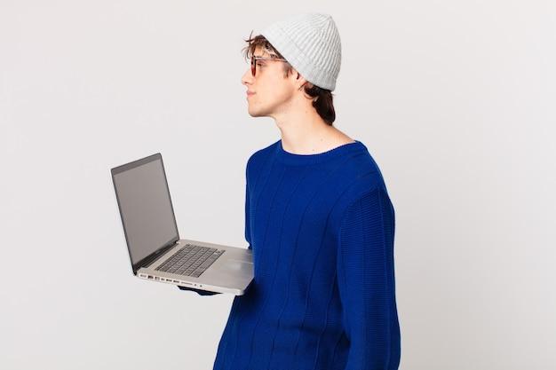 Jovem com um laptop na vista de perfil, pensando, imaginando ou sonhando acordado