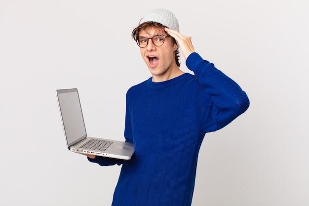 Jovem com um laptop parecendo feliz, espantado e surpreso
