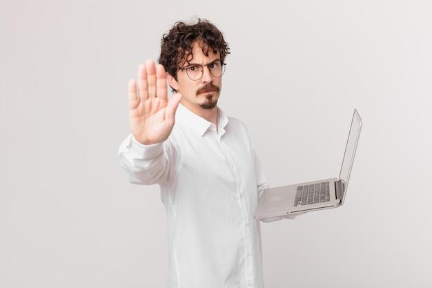 Jovem com um laptop parecendo sério, mostrando a palma da mão aberta fazendo gesto de pare