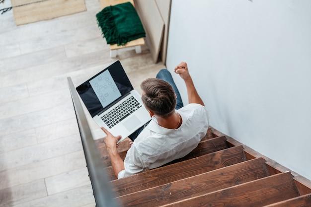 Jovem com um laptop sentado na escada de seu apartamento