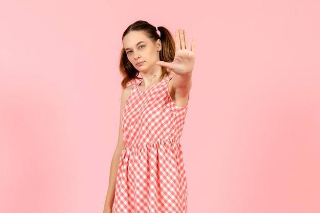Jovem com um lindo vestido rosa mostrando o sinal de pare no rosa