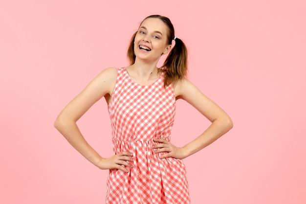 Jovem com um lindo vestido rosa posando e sorrindo na rosa
