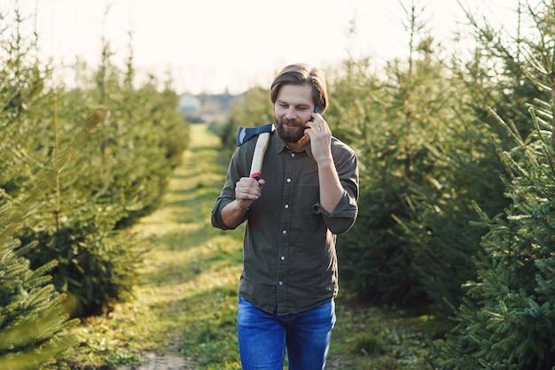 Jovem com um machado fala por smartphone escolhe árvores de natal na plantação se preparando para o
