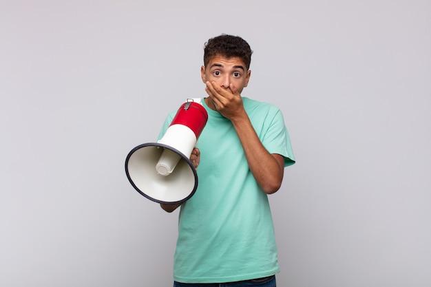Jovem com um megafone cobrindo a boca com as mãos com uma expressão chocada e surpresa, mantendo um segredo ou dizendo oops