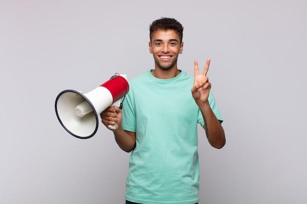 Jovem com um megafone sorrindo e parecendo amigável, mostrando o número dois ou o segundo com a mão para a frente, em contagem regressiva