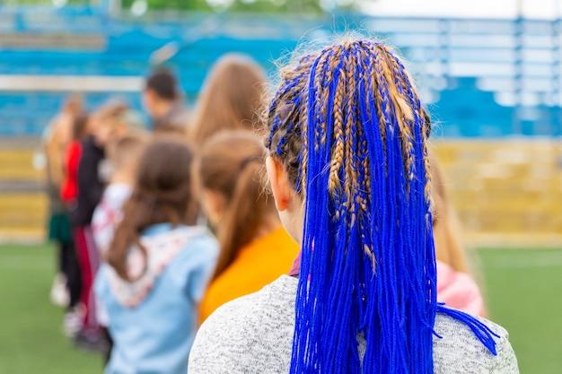 Jovem com um penteado elegante com fitas azuis trançadas no cabelo entre pares, cabelo azul. penteado incomum