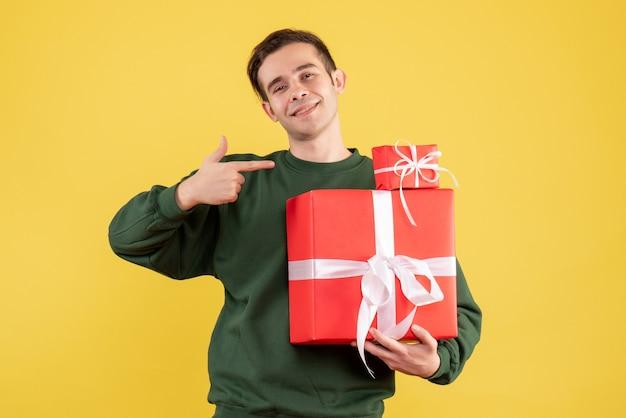 Jovem com um presente de natal apontando para os presentes de natal em um fundo amarelo.