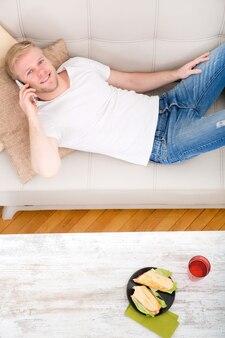 Jovem com um sanduíche no sofá