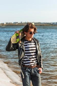 Jovem com um skate perto do mar