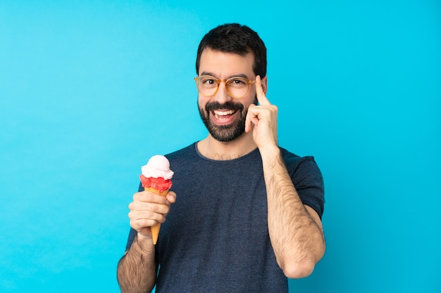 Jovem com um sorvete de corneta sobre azul com óculos e sorrindo