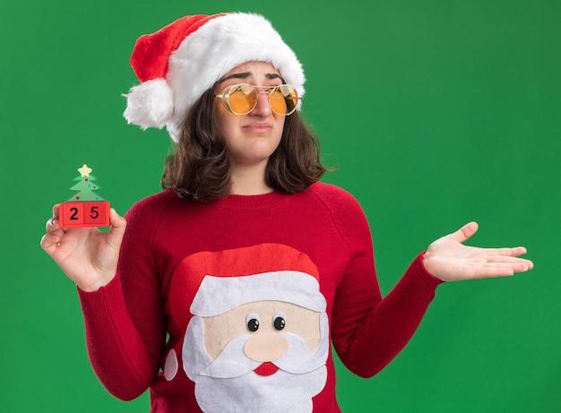 Jovem com um suéter de natal com chapéu de papai noel e óculos segurando cubos de brinquedo com o número 25 parecendo confusa com o braço levantado em pé sobre a parede verde