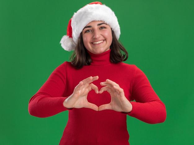 Jovem com um suéter vermelho e chapéu de papai noel sorrindo, fazendo um gesto de coração com os dedos em pé sobre a parede verde