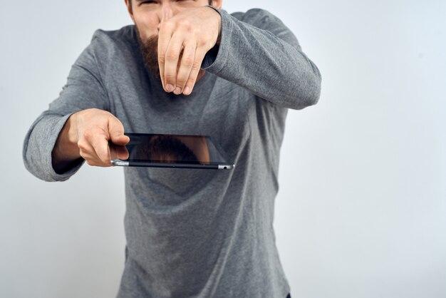 Jovem com um tablet eletrônico na mão em uma parede de luz