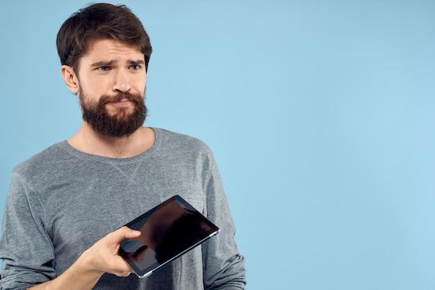 Jovem com um tablet eletrônico nas mãos em uma parede azul clara posando