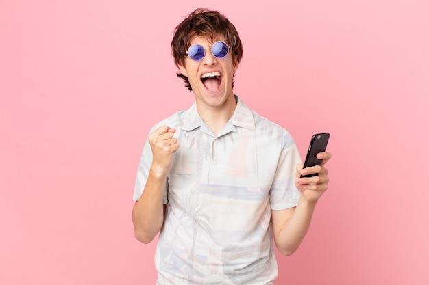 Jovem com um telefone celular chocado, rindo e comemorando o sucesso