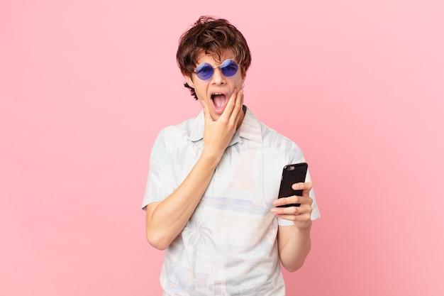 Jovem com um telefone celular com a boca e os olhos bem abertos e a mão no queixo
