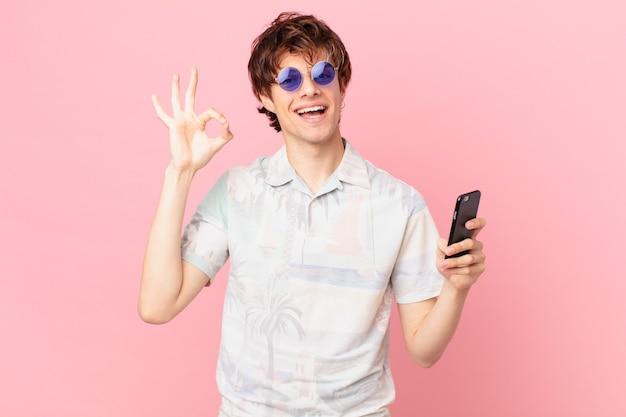 Jovem com um telefone celular feliz, mostrando aprovação com um gesto de ok