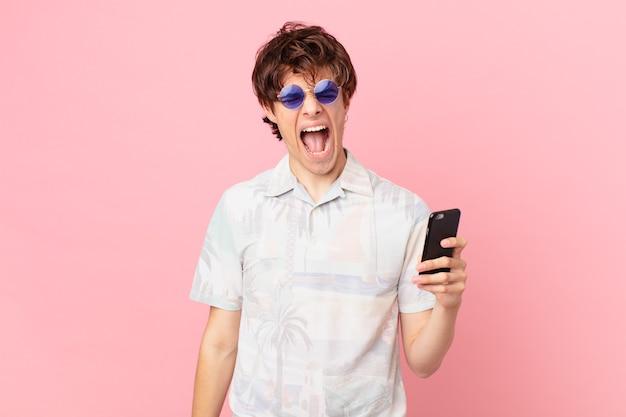 Jovem com um telefone celular gritando agressivamente parecendo muito zangado