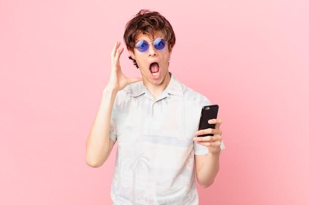 Jovem com um telefone celular gritando com as mãos para o alto