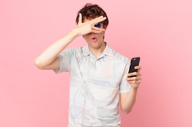 Jovem com um telefone celular parecendo chocado com medo ou apavorado cobrindo o rosto com a mão