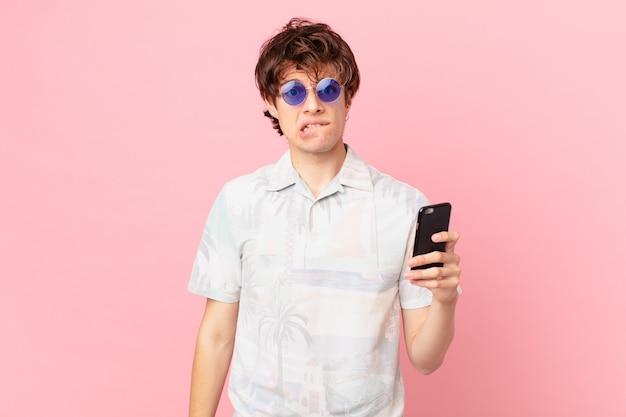 Jovem com um telefone celular parecendo perplexo e confuso
