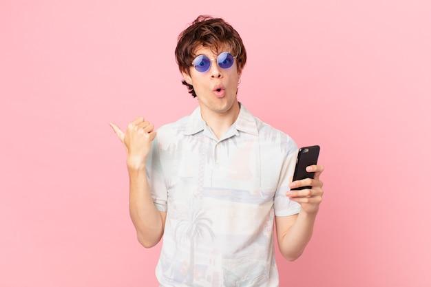 Jovem com um telefone celular parecendo surpreso com a descrença