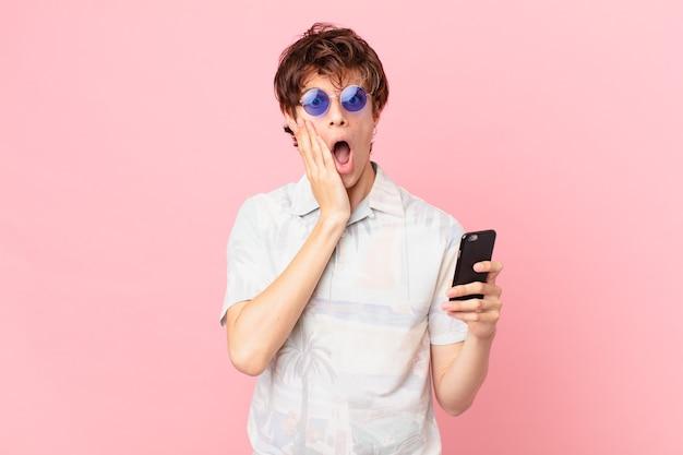 Jovem com um telefone celular se sentindo chocado e assustado