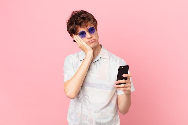 Jovem com um telefone celular se sentindo entediado, frustrado e com sono após um período cansativo