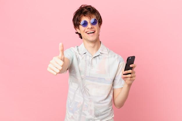 Jovem com um telefone celular se sentindo orgulhoso, sorrindo positivamente com o polegar para cima
