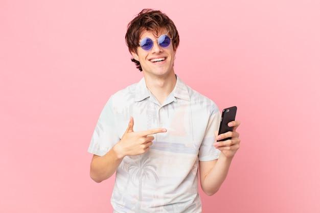 Jovem com um telefone celular sorrindo alegremente se sentindo feliz e apontando para o lado