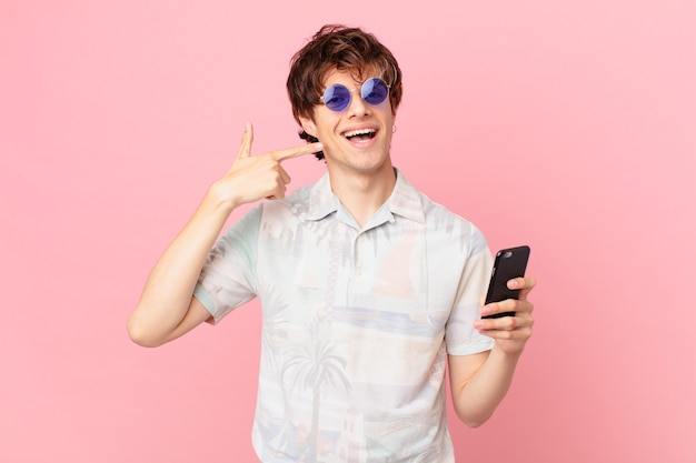 Jovem com um telefone celular sorrindo com confiança apontando para o próprio sorriso largo
